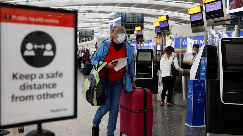 A passenger walks with her luggage at the Terminal 5 departures area at Heathrow Airport