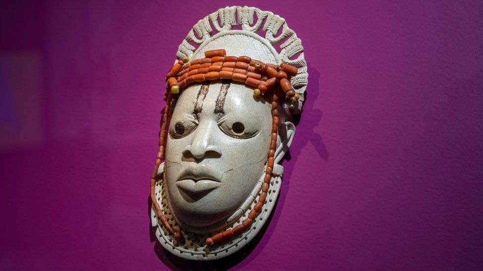 """A 19th-century ivory, ceremonial hip mask in honour of Queen Mother Idia and looted by British soldiers from the Kingdom of Benin in 1897 hangs on display in the """"Where Is Africa"""" exhibition at the Linden Museum on May 05, 2021 in Stuttgart, Germany."""