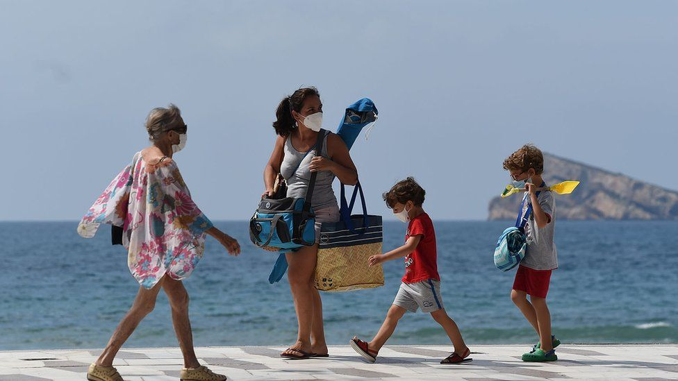 A family heading to the beach in face masks.