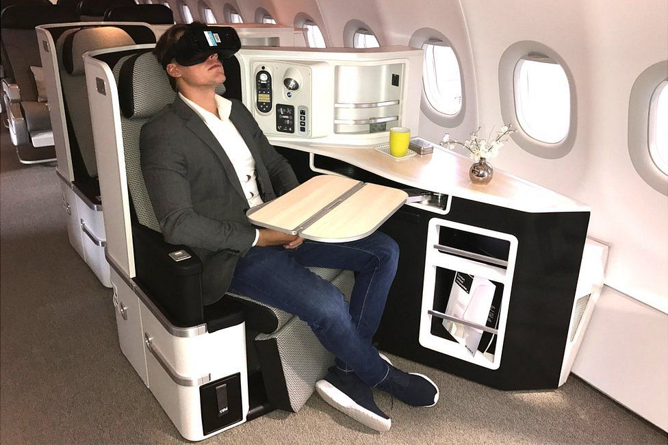 Man wearing VR headset in first class air cabin