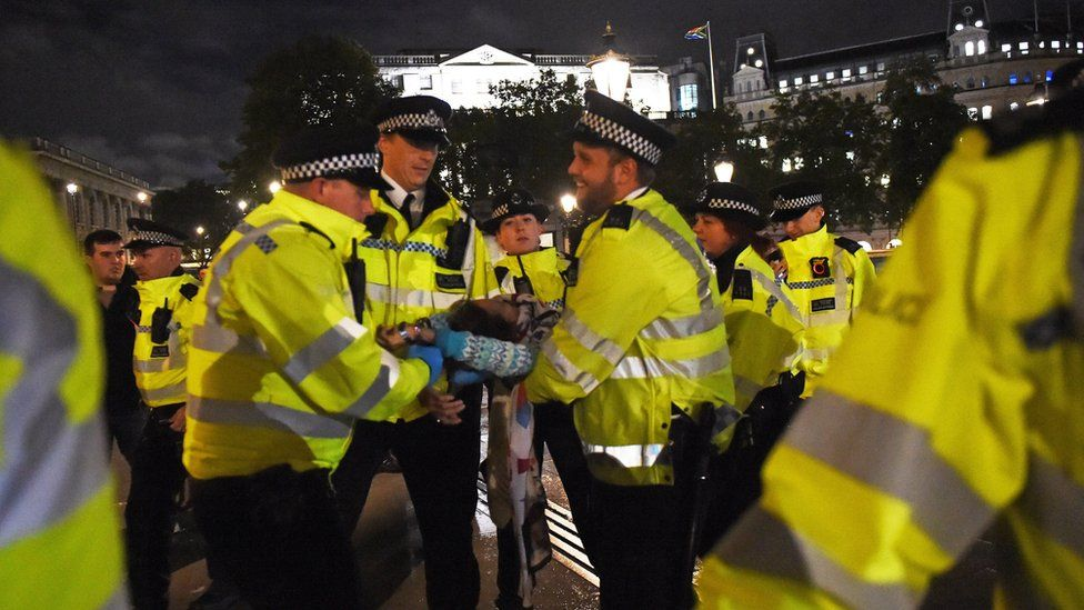 Police remove an Extinction Rebellion protester from Trafalgar Square in central London.