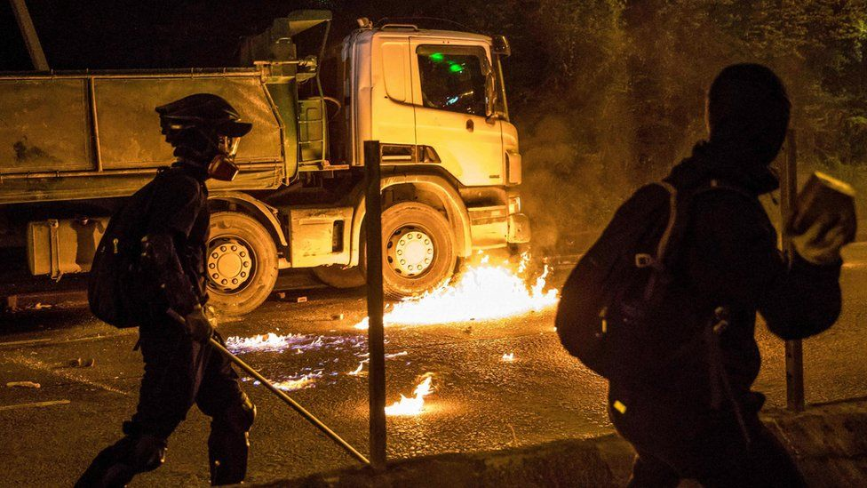 A petrol bomb thrown by a protester burns next to a truck after the driver attempted to drive through a blocked road outside the Hong Kong Polytechnic University on 14 November, 2019.