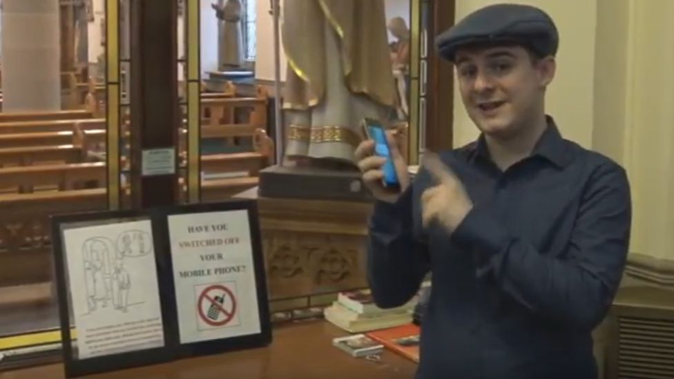 A man in a cap holding his phone in a church porch