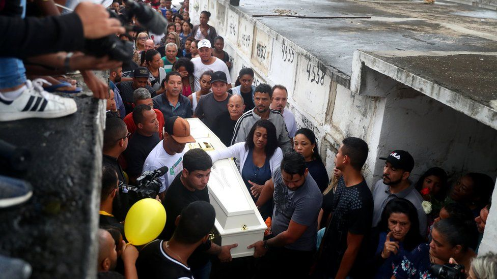 Relatives and friends watch as Ágatha's casket is carried at her funeral