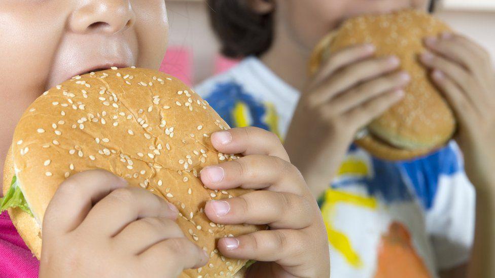 Two children eat burgers