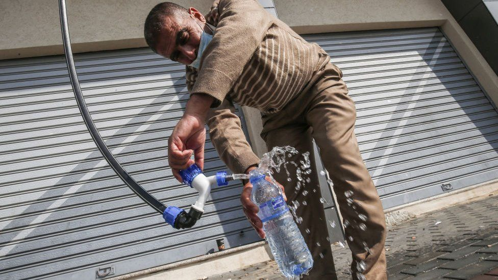 A man pouring water into a plastic bottle