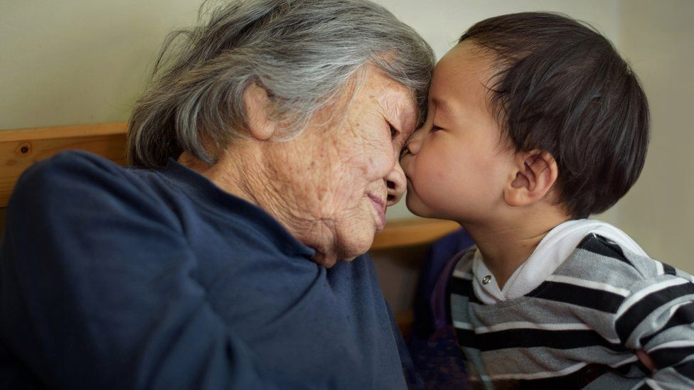 A Chinese child kisses an older woman - stock image