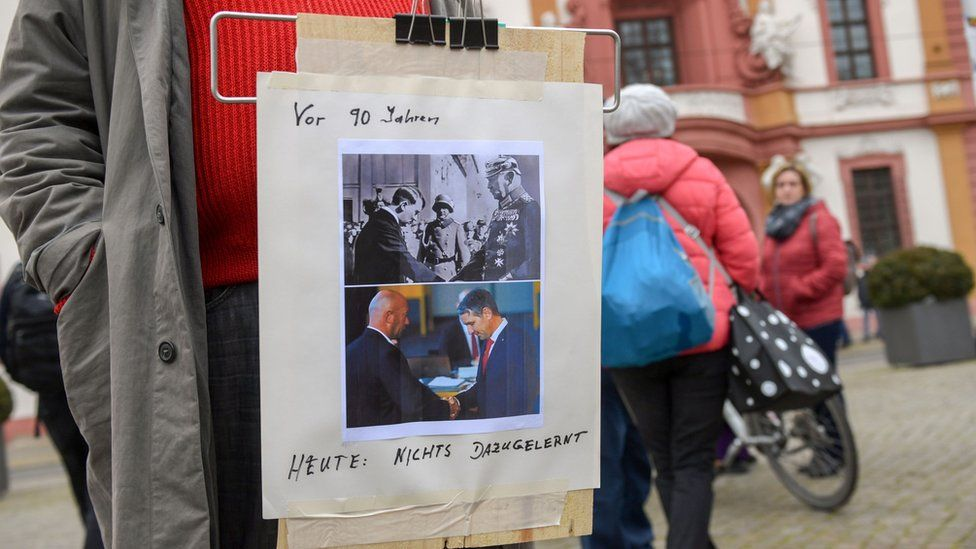 A protester in Germany bearing an image comparing the recent Thuringia leader's election with Adolf Hitler's