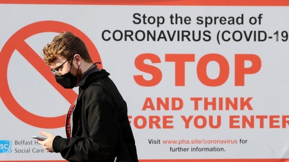 A young man wearing a mask looking at his phone and walking in front of a Covid-19 awareness poster from the Department of Health