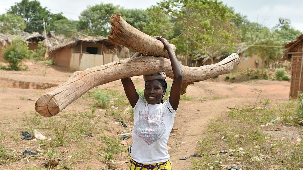 woman smiles as she carries long pieces of firewood