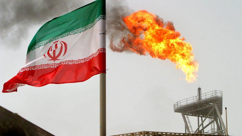 an Iranian flag near an oil flare