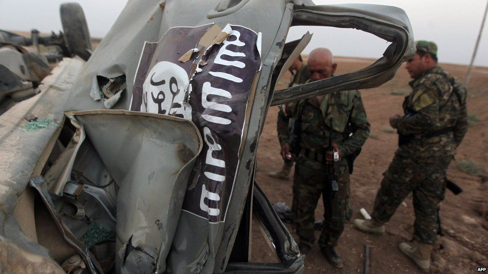 Peshmerga fighters inspect the remains of a car which belonged to Islamic State (IS) militants after it was targeted by an American air strike in the village of Baqufa, north of Mosul, on 18 August 2014.