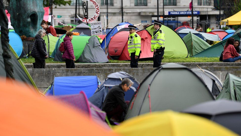 Police officers walk amongst tents at the Extinction Rebellion group's environmental protest camp at Marble Arch in London