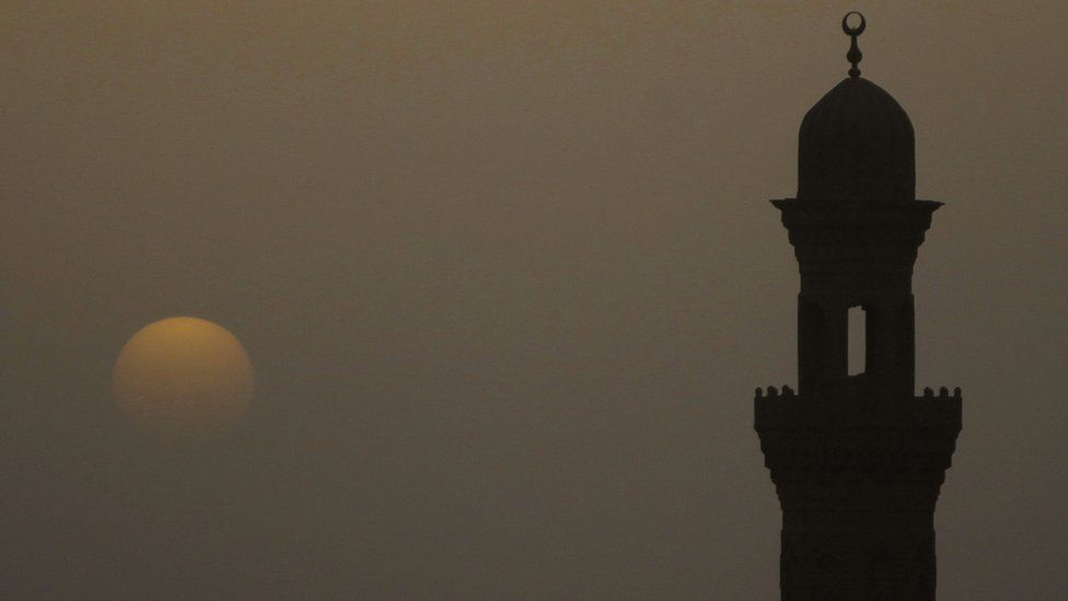 Minaret of a mosque is pictured during sunset on a hazy day in Cairo, April 8, 2013