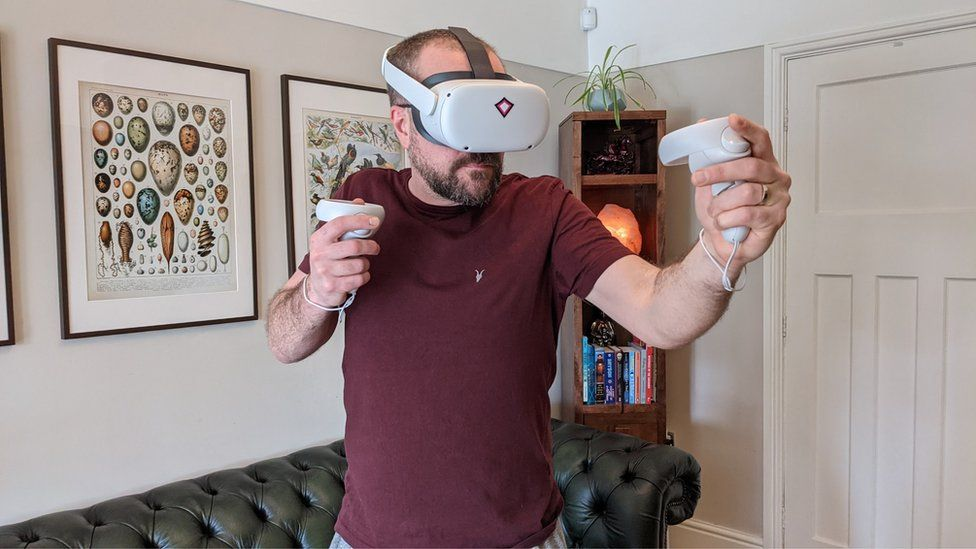 John Bevan enjoys rock climbing in virtual reality using a headset gifted by his employer