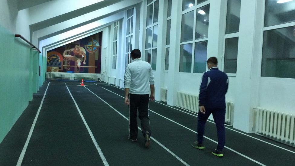 Two men walk on an indoor track in Kursk