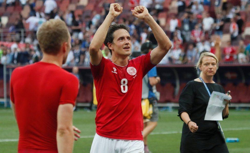 Danish international footballer Thomas Delaney raises his fists above his head in celebration