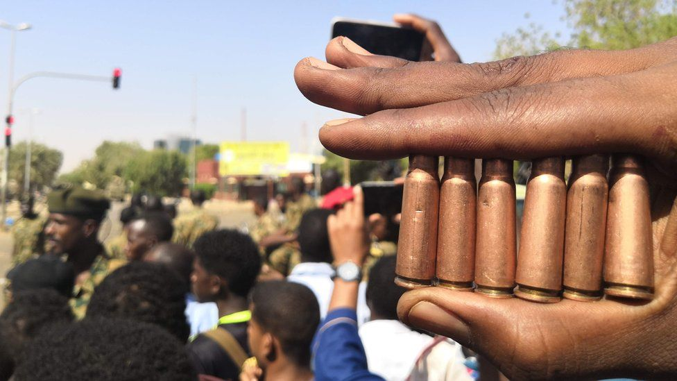 A Sudanese protester shows bullet cartridges as others gather in front of security forces during a demonstration in the area of the military headquarters in the capital Khartoum on April 8, 2019.
