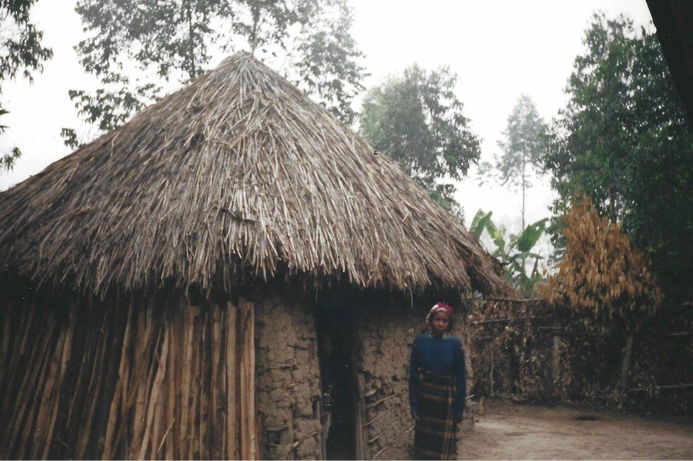 Peter's mother stands outside the house where he grew up