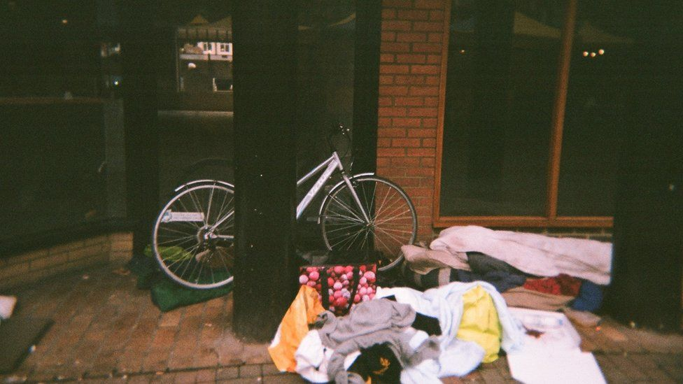 A bike, bags and bedding on the street outside a building