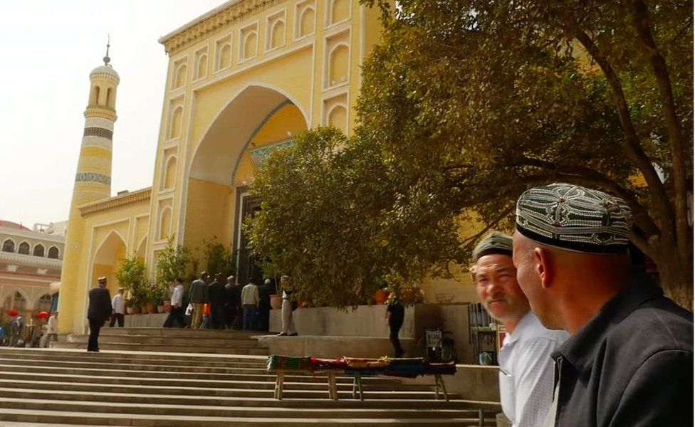 The Id Kah mosque, with worshippers passing by