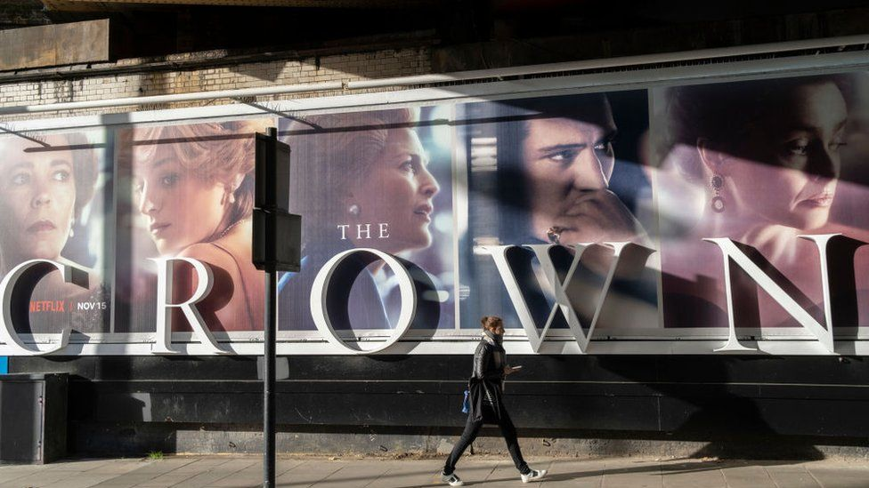 A woman walks in front of a billboard for The Crown