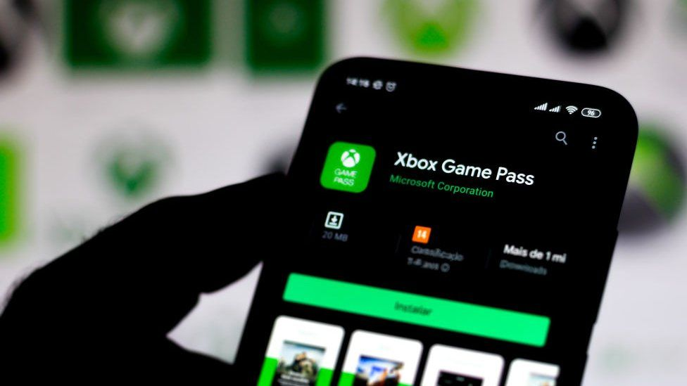 The Xbox Game Pass app is seen on a phone screen against a blurred background