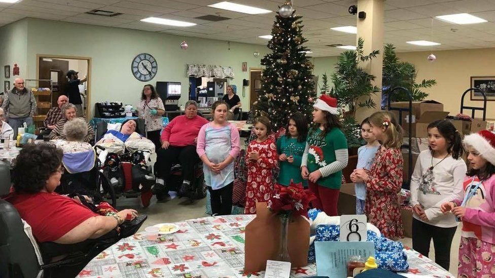 Girls scouts sang carols to residents at Fort Hudson nursing home on Friday when they received their bags