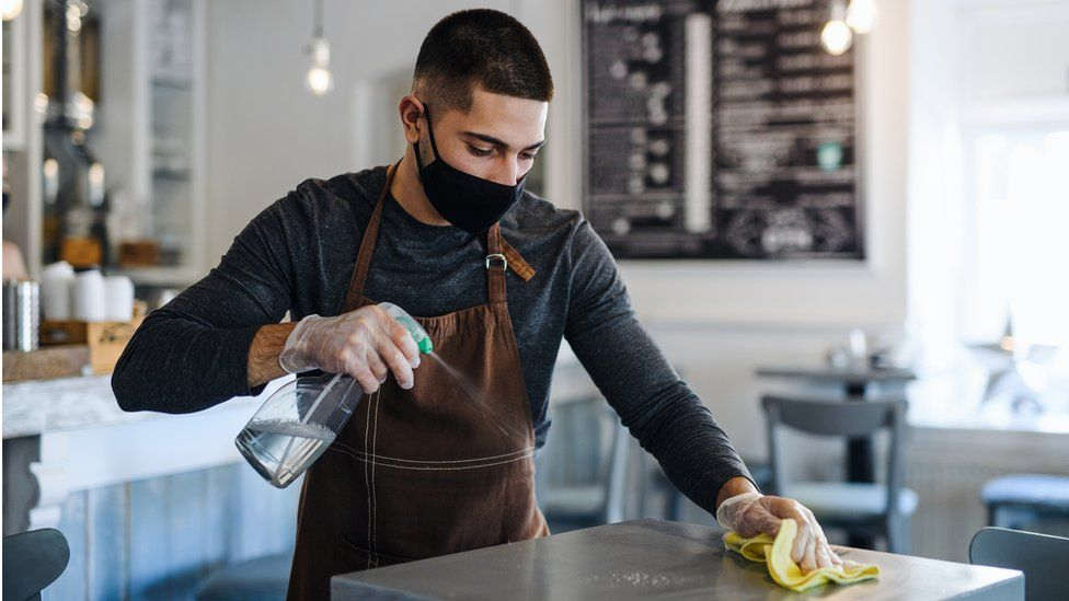 Waiter cleans table