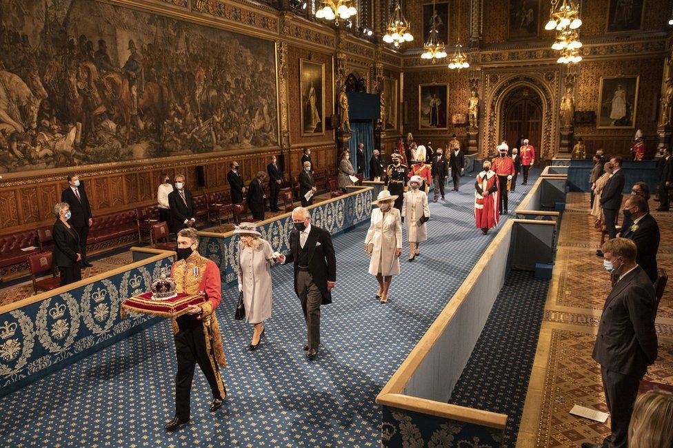 """Queen Elizabeth II, accompanied by the Prince of Wales, proceeds through the Royal Gallery before delivering the Queen""""s Speech during the State Opening of Parliament in the House of Lords at the Palace of Westminster in London"""
