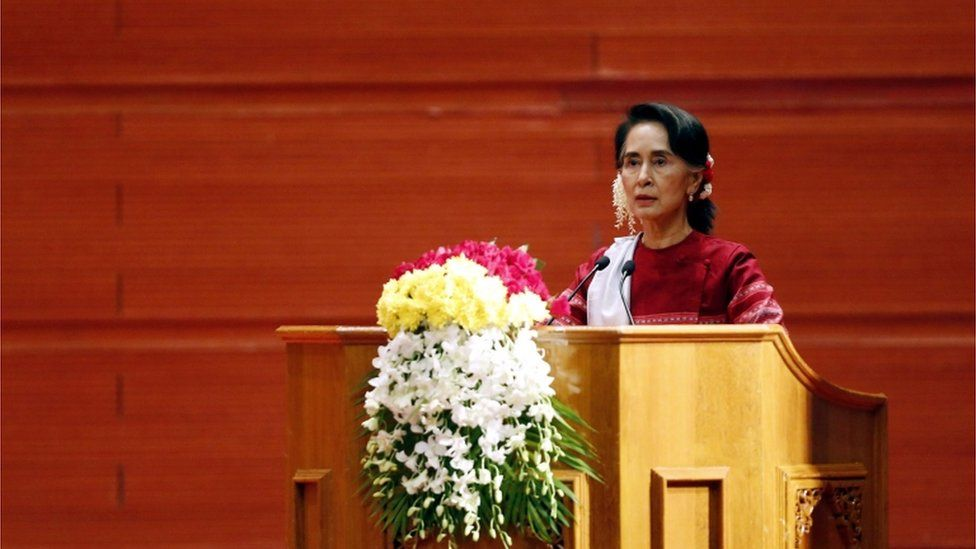 Aung San Suu Kyi speaking at a podium
