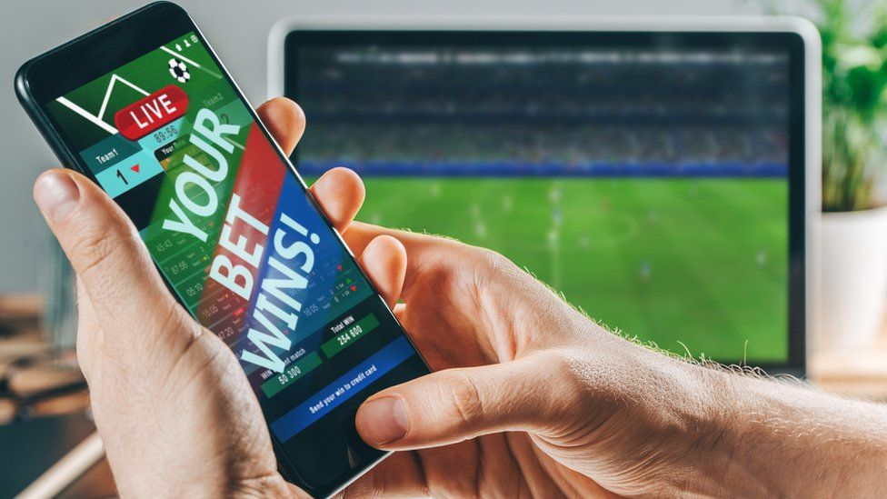 Phone with winning of a bet in front of football on a screen