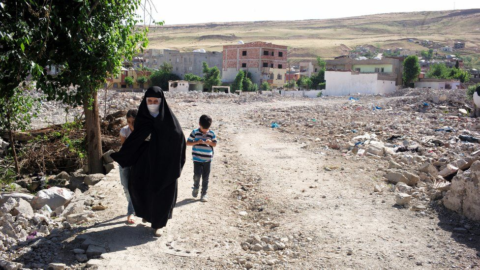 Woman walks with her two children along a street in Cizre, Turkey - May 2016