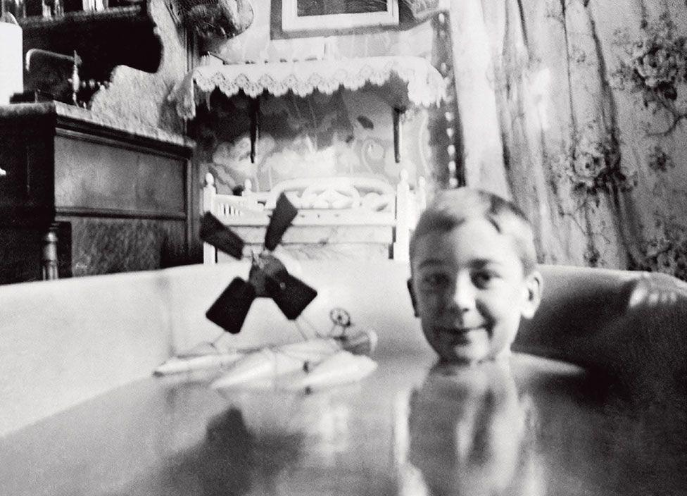 Jacques Henri Lartigue sits in a bath with a toy plane