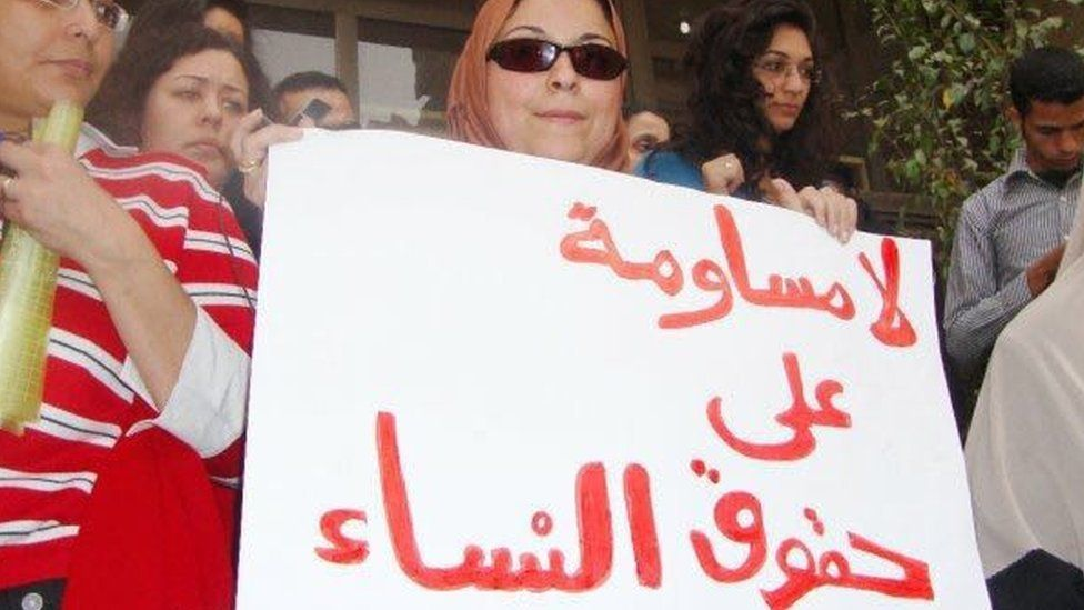 "Esraa Abdel Fattah holds a sign reading: ""No negations on women rights"""
