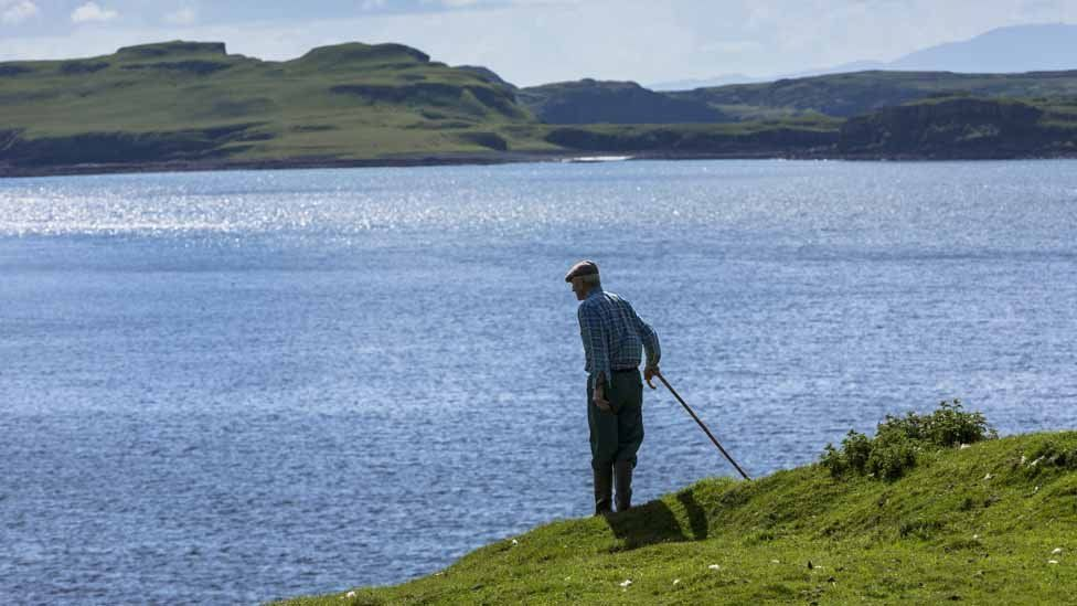 A farmer looks out over Loch Harport near Coillure on Isle of Skye