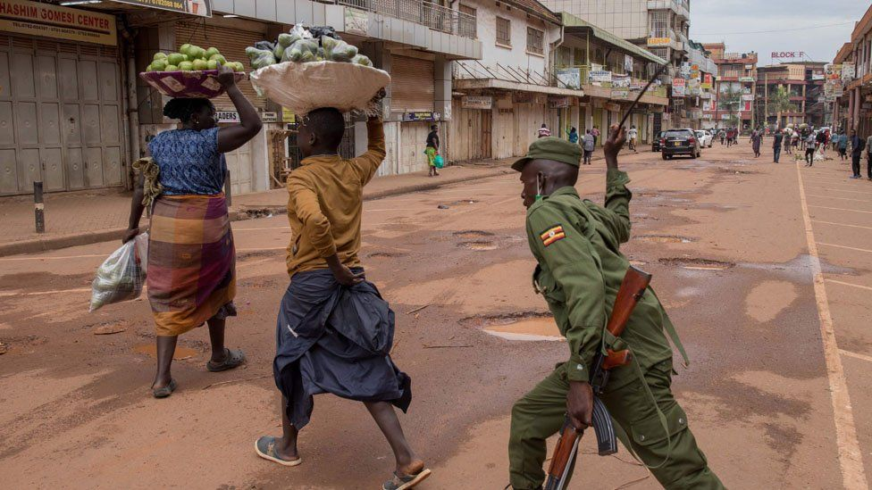 A police officer beats a female orange vendor on a street in Kampala, Uganda, on March 26, 2020, after Ugandan President Yoweri Museveni directed the public to stay home for 32 days