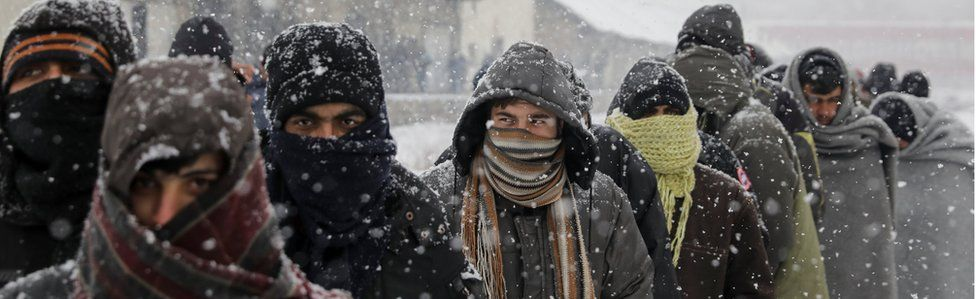 Migrants wait in line to receive free food during a snowfall outside a derelict customs warehouse in Belgrade (9 Jan)