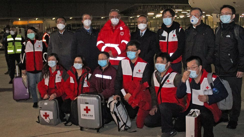 """Chinese medics posing for a group photo after landing on a China Eastern flight on March 13 at Rome""""s Fiumicino international airport from Shanghai, bringing medical aid to help fight the new coronavirus in Italy"""