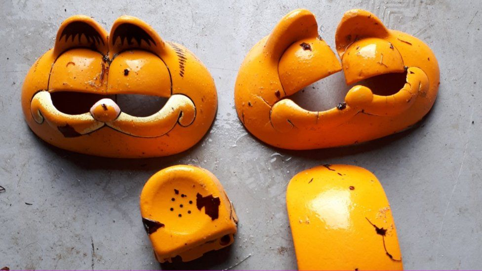 The plastic remnants of multiple Garfield phones - with vacant eye sockets starting from the face piece and a broken earpiece among them