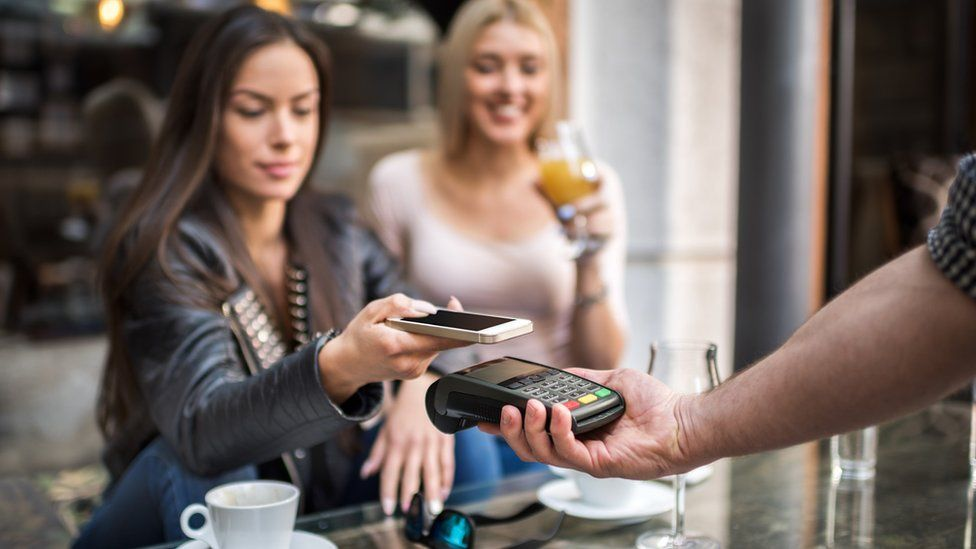 You woman paying with a smartphone