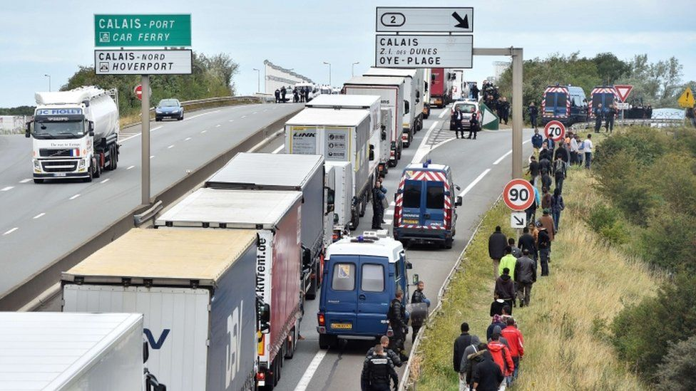 Lorries queuing for the port at Calais in August and watched by migrants