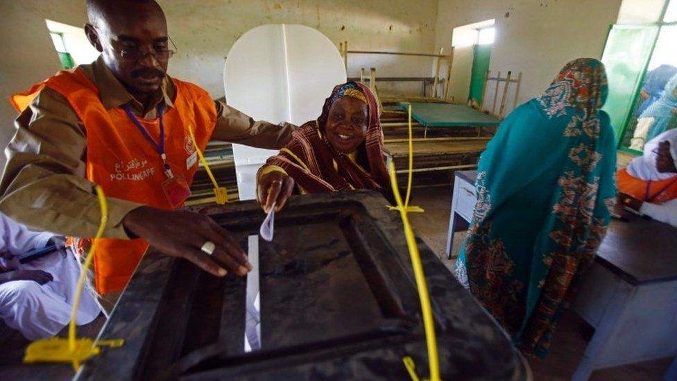 A woman casts her vote, with the help of an election official