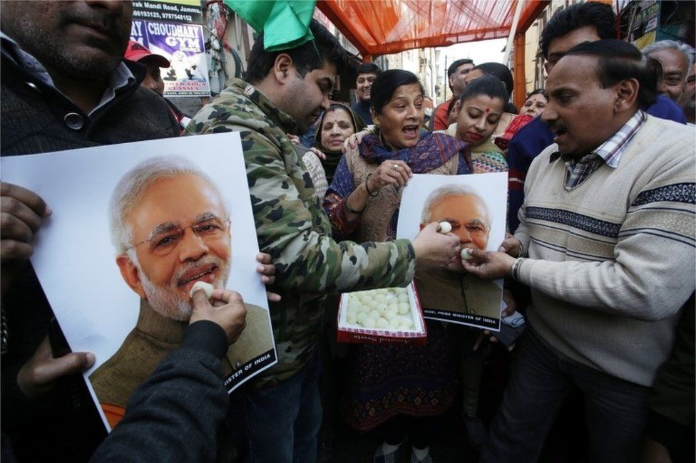 Indian people feed sweets to a poster of Indian Prime Minister Narendra Modi as they celebrate the Indian Air Force's air strike across the Line of Control (LoC) near the international border with Pakistan; in Jammu, the winter capital of Kashmir, India, 26 February