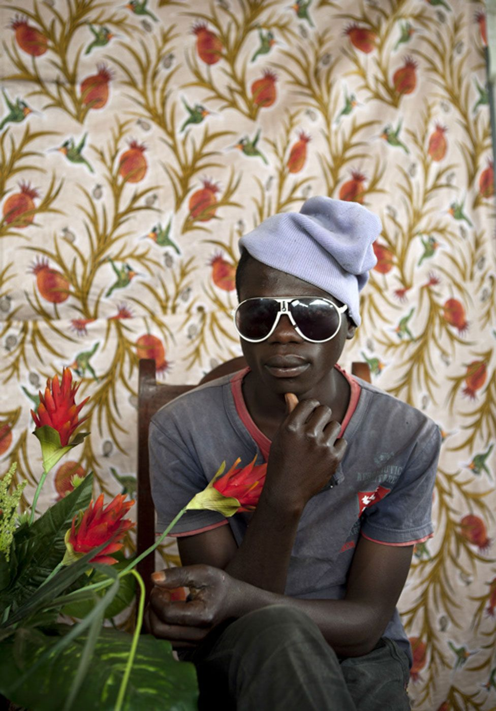 Boy in a beanie and sunglasses poses with flowers