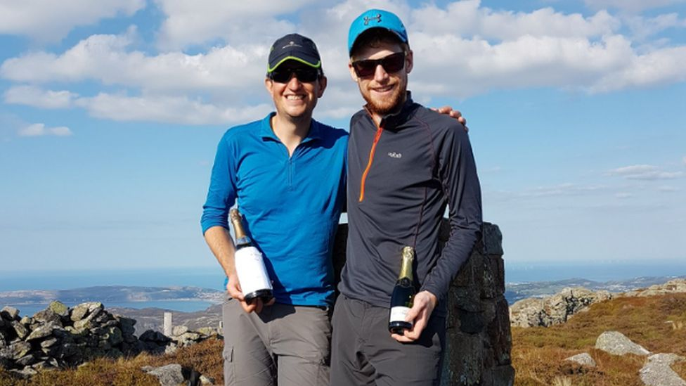 Mike and Matt standing on top of Tal y Fan with a bottle of champagne each