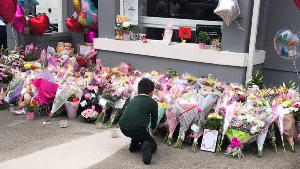 A young boy lays a floral tribute to Saffie Roussos