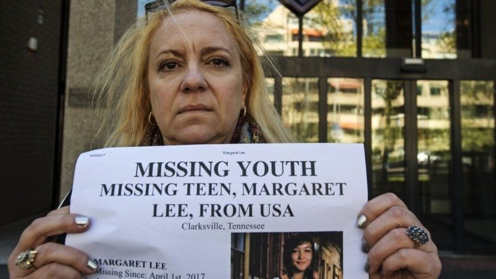 Sabrina Lee, the mother of missing Margaret Lee, poses with a missing poster of her daughter.