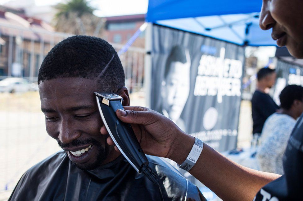 """A youth has his haircut as part of the centenary celebrations of the birth of South Africa's first black leader Nelson Mandela following the theme """"Be the Legacy"""", a call to action for all citizens of the world to live the values of """"Madiba"""" a Xhosa title of respect for Mandela, in Johannesburg, on June 30, 2018. The Nelson Mandela Foundation launched with the Philips South Africa, the Shave to Remember campaign (#ShaveToRemember) which calls on people to honour the values embodied by the international icon Nelson Mandela by wearing his haircut. The first president of the """"rainbow nation"""" Nelson Mandela was born on July 18, 1918 in Mvezo, Eastern Cape, and died December 5, 2013 in Johannesburg"""