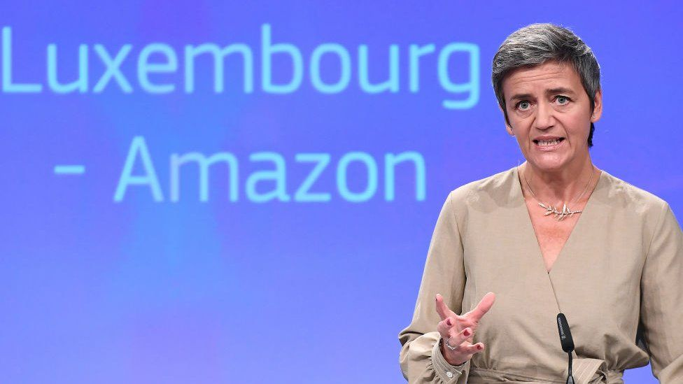Margrethe Vestager addresses a press conference, with the words Luxembourg - Amazon on a screen behind her